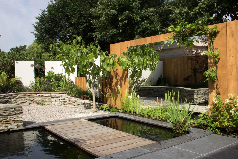 Rustgevende achtertuin met koivijver en verticale plantenmuur for Tuin en vijver