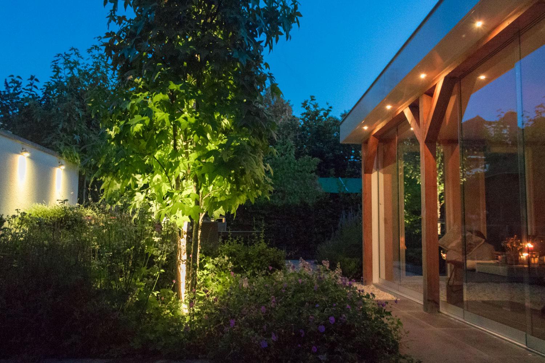 Verschillende soorten tuinverlichting aan de wand, onder de boom en op de veranda.